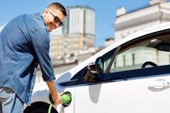 Glad stilig man som rymmer en bränsledysa royaltyfri foto