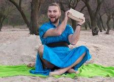 Glad stilig skäggig man i blått kimonosammanträde som svänger den stora boken och ser kameran arkivfoto