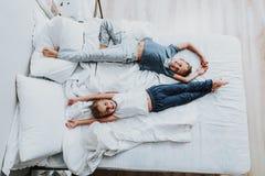 Glad syskongrupp som lägger på säng och att ha gyckel arkivbilder