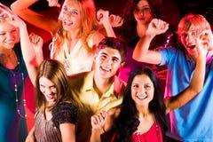 Glad teens. Joyful teens enjoying themselves in night club while dancing Stock Images