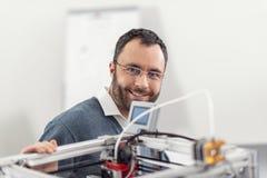 Glad tekniker i glasögon som poserar nära skrivaren 3D Arkivbild