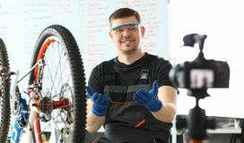 Glad tekniker Taking Care av bergcykeln arkivbild