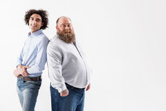 Glad thin and thick guys laughing. Different but happy. Portrait of joyful slim boy is standing and leaning back on fat bearded man. They are looking at camera Stock Photos