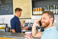 Glad to hear you. Coffee take away option for busy people. Man mobile conversation cafe barista background. Drink coffee royalty free stock image