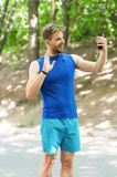 Glad to see you. Athlete mobile phone video call before running. Man athlete smiling face online training see coach. Nature background. Sportsman online video Stock Photos