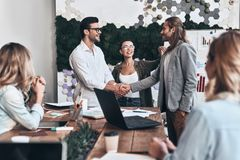 Glad to work with you!. Young modern men in smart casual wear shaking hands and smiling while standing in the creative office stock photography