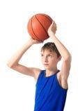 Glad tonåring som rymmer en boll för basket över hans huvud Är Royaltyfri Foto