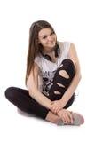 Glad tonåringflicka med att sitta för hörlurar Fotografering för Bildbyråer