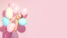 Glad tonårs- flicka för skönhet med färgrika luftballonger som har gyckel arkivbild