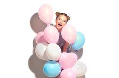 Glad tonårs- flicka för skönhet med färgrika luftballonger som har gyckel arkivfoto