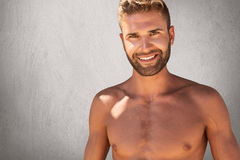 Glad topless male with trendy hairstyle and bristle having strong body builduing posing against grey background with happy express. Ion. Attractive male model Stock Photo