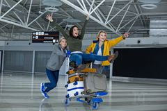Glad tourists wheeling on luggage trolley. Back to the childhood. Portrait of happy women having a good time at the airport. They are rolling each other on a Stock Images