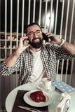 Glad trevlig man som samtidigt använder två smartphones fotografering för bildbyråer