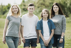 Glad two girls and two boys taking a walk. Glad two girls and two boys teenagers friends taking a walk together outdoors stock photos