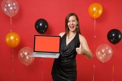 Glad ung flicka i svart klänningvisningtumme upp och rymma bärbar datorPCdatoren med den tomma svarta tomma skärmen på rött royaltyfria foton