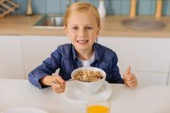 Glad ung flicka som äter den sunda frukosten Royaltyfri Bild