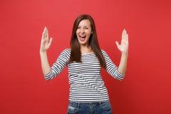 Glad ung kvinna som gör en gest visa format med horisontalkopieringsutrymme och hålla brett öppet för mun isolerat på rött arkivfoton