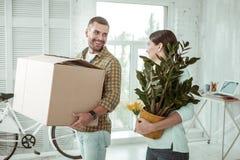 Glad ung kvinna som rymmer en grön växt arkivfoton