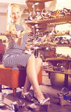 Glad ung kvinna som väljer två par av nya skor Arkivfoton