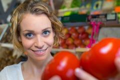 Glad ung kvinnlig kund som väljer nya mogna tomater på marknad Arkivbild