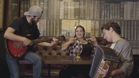 Glad ung le skäggig man som spelar gitarren i stången, hans vän som spelar dragspelet medan attraktiv fyllig kvinna stock video