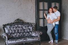 Glad ung man och härlig en gravid kvinna som kramar sig Vi ser de och kramar midsectionen royaltyfria foton
