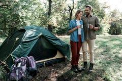Glad ung man och kvinna som tycker om te i naturen Arkivfoton
