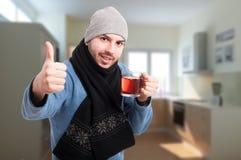 Glad ung man som dricker te och visar thumbup Arkivfoto