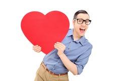 Glad ung man som rymmer en stor röd hjärta Arkivbilder