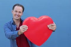 Glad ung man som rymmer en stor röd hjärta isolerad på blå bakgrund Royaltyfri Bild