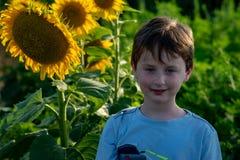 Glad ung pojke för skönhet med solrosen som tycker om naturen och skrattar på sommarsolrosfält Sunflare solstrålar, glöd arkivfoto