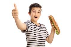 Glad ung pojke som rymmer en smörgås och ger upp en tumme Royaltyfria Bilder