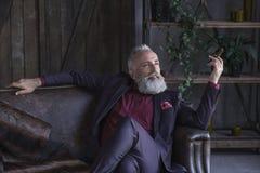 Glad Unshaven Old Businessman Smoking Cigar Royalty Free Stock Images