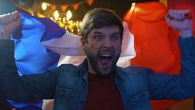 Glad vinkande flagga f?r sportfan av Frankrike i bar som jublar favorit- lagseger arkivfilmer
