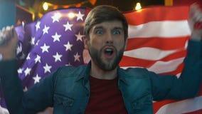 Glad vinkande flagga f?r sportfan av USA i bar som jublar favorit- lagseger stock video