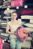 Glad woman choosing blanket. In bedding section in shop Royalty Free Stock Photography