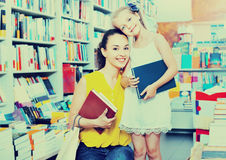 Glad woman with girl taking literature books Stock Photos
