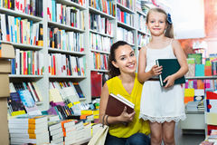 Glad woman with girl taking literature books Royalty Free Stock Image