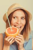Glad woman in hat eating biting grapefruit. Royalty Free Stock Image