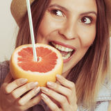 Glad woman in hat eating biting grapefruit. Royalty Free Stock Photo
