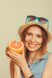 Glad woman in hat and sunglasses with grapefruit Stock Photos