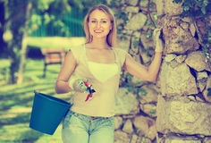 Glad woman having horticultural instruments in garden. Happy smiling  blond woman having horticultural instruments in garden on summer day Royalty Free Stock Image