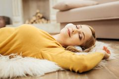 Glad woman listening to music with her eyes closed. Feeling great. Beautiful content young blond woman smiling and listening to music and wearing headphones Royalty Free Stock Photos