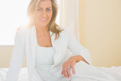 Glad woman looking at camera posing on her bed Stock Photography