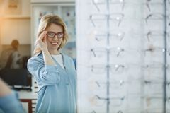 Glad woman looking at mirror with spectacles. Outgoing lady admiring reflection in optician shop while holding eyeglasses by arm. Optics concept Royalty Free Stock Photo