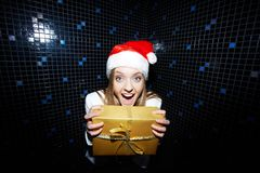 Glad woman. Portrait of glad businesswoman in Santa cap holding Chistmas gift Stock Images