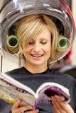 Glad woman reading with hair curlers under hairdry