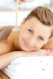 Glad woman receiving a beauty treatment with mud Royalty Free Stock Image