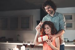 Glad woman receiving present from man at home. Portrait of happy married couple celebrating anniversary in kitchen. Husband is holding a gift box in front of his Stock Photo