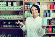 Glad woman seller holding box with nutrients Royalty Free Stock Photos